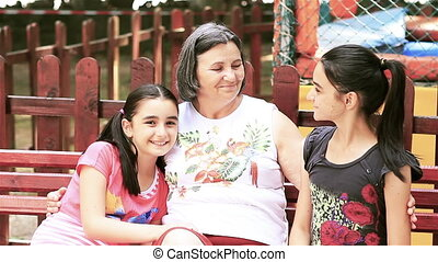 Senior woman with granddaughters looking at camera