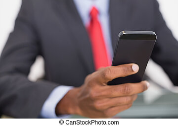 Mid section of well dressed businessman text messaging -...