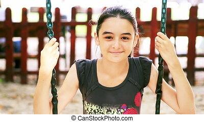Teenage girl on swing smiling