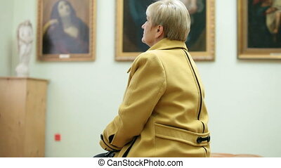 Visit Art Gallery - Mature woman looking at paintings in the...