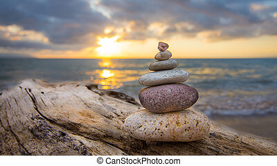 Zen Stones on a tree trunk and sunset in the background.