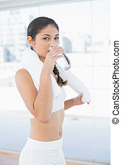 Woman with towel around neck drinking water - Portrait of a...