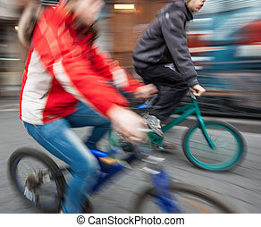 Two young boys on bicycles in the city. Intentional motion...