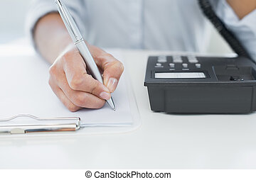 Mid section of woman using telephone while writing on...