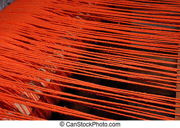 threads - thic red theads strained in the loom