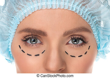Plastic surgery. Cropped image of female face with marks on...