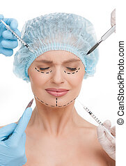 Plastic surgery. Terrified young woman keeping eyes closed...