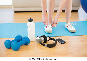 Female tying shoes with sporty equipment in fitness center -...