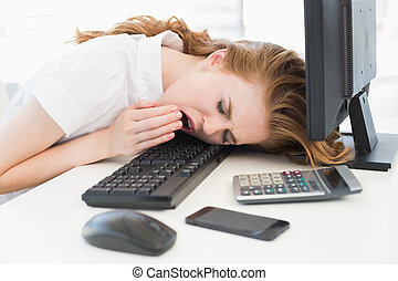 Asleep businesswoman yawning on keyboard at office - Young...
