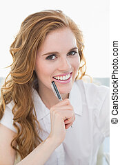 Portrait of smiling businesswoman with pen