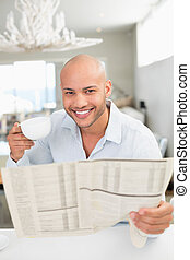 Smiling man with coffee cup reading newspaper at home -...
