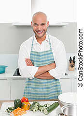 Smiling young man with vegetables in kitchen - Portrait of a...