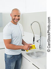 Smiling young man doing the dishes at kitchen sink -...