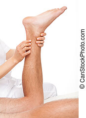Calf massage - Physiotherapist massaging man's calf on white...