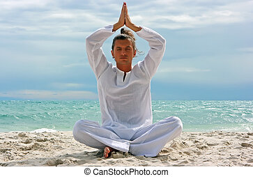 Yogi on the beach - Young man practising yoga on the sandy...
