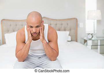 Thoughtful bald man sitting on bed - Thoughtful young bald...
