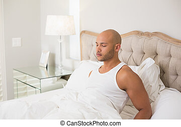 Relaxed young bald man with eyes closed in bed - Side view...