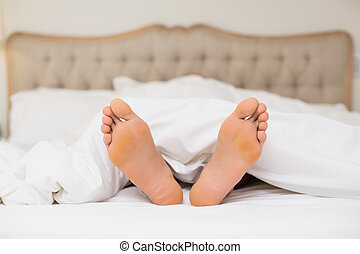 Bare feet in bed at home - Close up of bare feet in bed at...