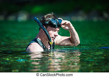 Young Adult Snorkeling in a river with Goggles and Scuba