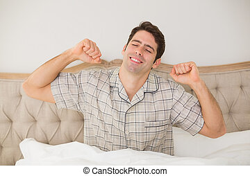Man waking up in bed and stretching