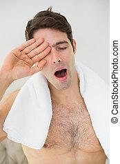 Shirtless man yawning as he rubs his eye - Close up of a...