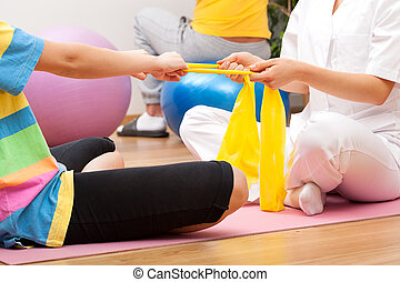 Exercises with the patient - Physiotherapist exercising with...