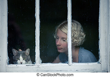Woman and Cat Looking at the Rainy Weather By the Window...