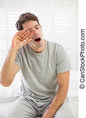 Sleepy man yawning as he rubs his eye in bed - Sleepy young...