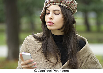 Text messaging - Woman standing in a park a message by phone...
