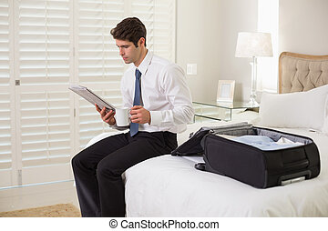 Young businessman with coffee cup reading newspaper by luggage at a hotel room