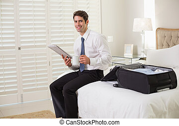 Smiling young businessman with coffee cup reading newspaper by luggage at a hotel room