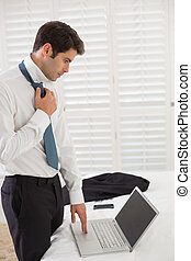 Businessman wearing tie while using laptop at a hotel room -...