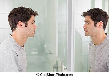 Tensed man looking at self in bathroom mirror