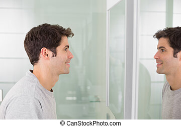 Young man smiling at self in bathroom mirror