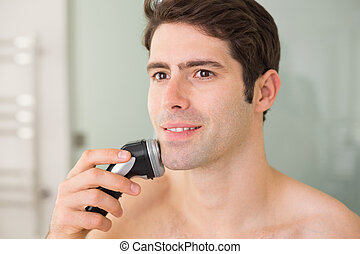 Smiling handsome shirtless man shaving with electric razor -...