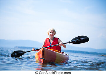 Woman With Safety Vest Kayaking Alone on a Calm Sea - Young...