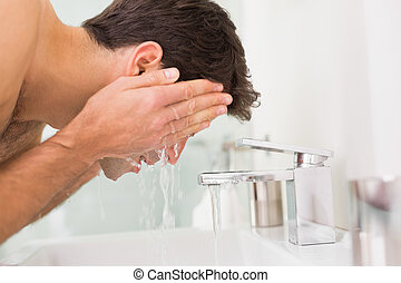 Shirtless young man washing face in bathroom - Side view of...