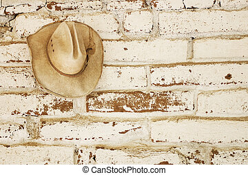 Hat on the wall - a straw cowboy hat hanging on an brick...
