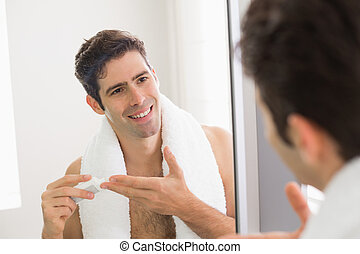 Man with reflection putting moisturizer on his face - Close...