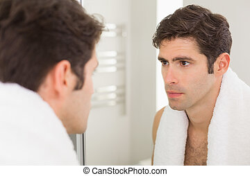 Serious young man looking at self in bathroom mirror - Close...