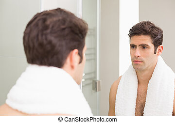 Tensed young man looking at self in bathroom mirror - Rear...