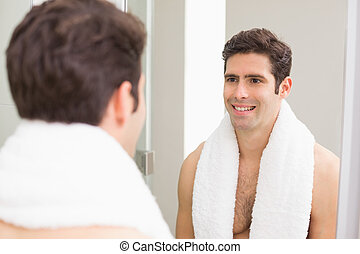 Rear view of man smiling at self in bathroom mirror