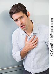 Portrait of a casual young man with chest pain standing at...