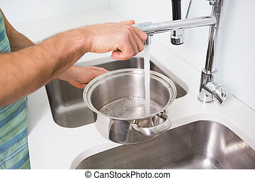 Hands filling pan with water at kitchen sink - Close up of...