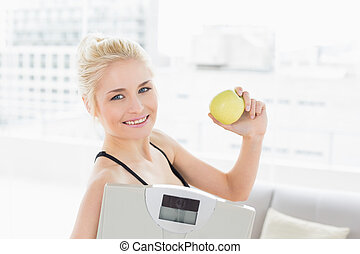Fit woman holding scale and apple in fitness studio -...