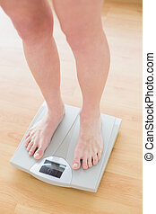 Close up of woman standing on weighing scale in a fitness...