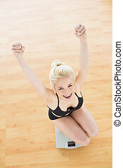 Cheerful fit woman on scale in fitness studio - Overhead...