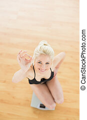 Cheerful woman gesturing ok sign on scale in fitness studio...