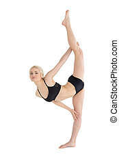 Full length of a sporty young woman stretching body against...