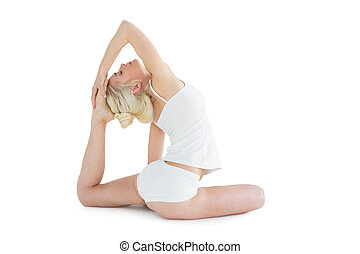 Toned young woman doing the pigeon pose - Full length side...